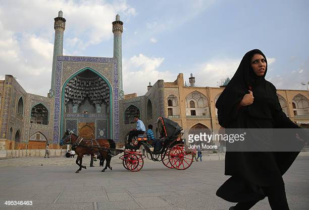 People ride a horse and carriage in Isfahan's Unescolisted central square on June 2 2014 in Isfahan Iran Isfahan with its immense mosques picturesque...