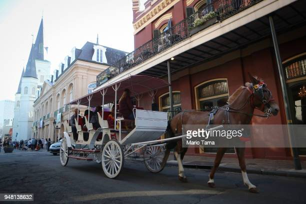 People ride a horsedrawn carriage in the historic French Quarter the first neighborhood of the city on April 16 2018 in New Orleans Louisiana New...