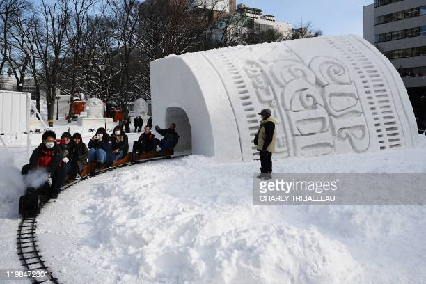 People ride a mini steam locomotive through the Cup Noodles and Rui Hachimura's snow tunnel during the Sapporo Snow Festival on February 4 2020 The...