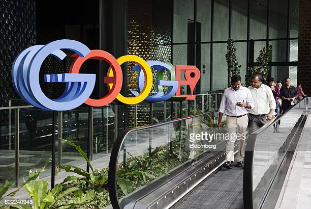 People ride a moving walkway in front of a sign featuring Google Inc's logo at the company's AsiaPacific headquarters during its opening day in...