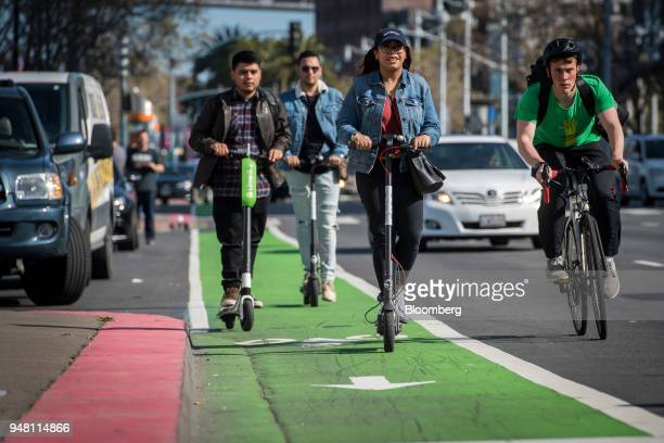 People ride a Neutron Holdings Inc LimeBike left and Bird Rides Inc shared electric scooters on the Embarcadero in San Francisco California US on...