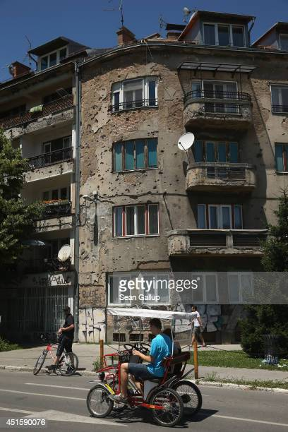 People ride a pedal quad past an apartment building still heavily scarred by bullet holes from the 1992-1995 Bosnian War on June 29, 2014 in...
