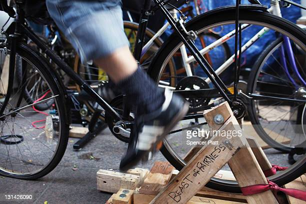 People ride a stationary bicycle to generate electricity for laptops and mobile phones at the headquarters of the 'Occupy Wall Street' movement in...