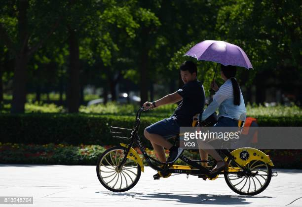 People ride a tandem bicycle on July 12 2017 in Beijing China The dog days of summer start from July 12 in China