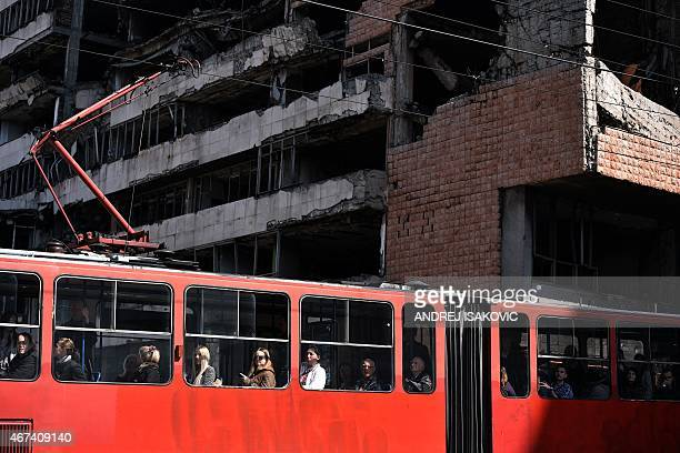 People ride a tram past the building of the former federal Interior Ministry in Belgrade which was destroyed during the 1999 NATO air campaign...