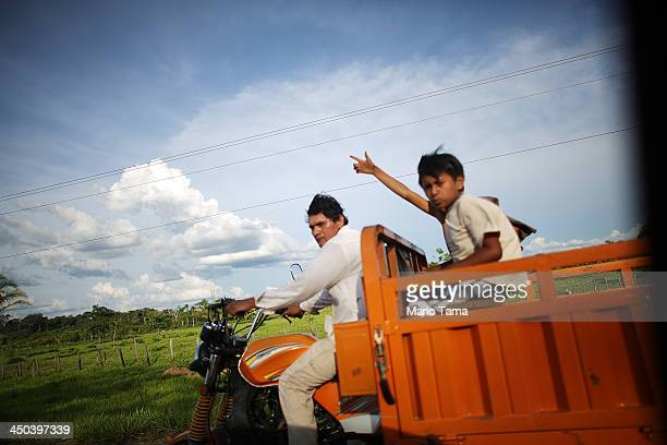 People ride along a deforested section on the Interoceanic Highway in the Amazon lowlands on November 16 2013 in Madre de Dios region Peru The...