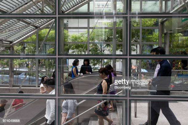 People ride an escalator and descend a flight of stairs to a MRT station in the central business district of Singapore on Wednesday June 13 2018...