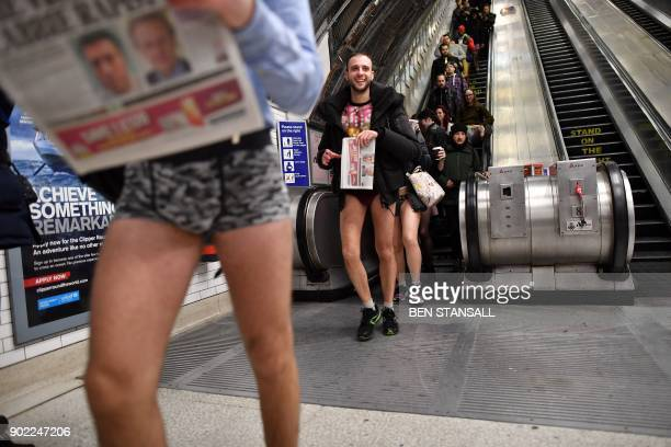 People ride an escalator as they take part in the annual 'No Trousers On The Tube Day' at Liverpool Street Station in London on January 7, 2018....