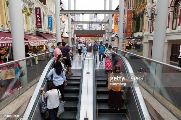 People ride an escalator in the Chinatown area of Singapore on Wednesday June 13 2018 Tourism as well as the consumer sector will likely see a lift...