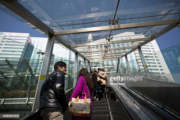 People ride an escalator in the Luohu district of Shenzhen China on Thursday Dec 19 2013 Two of Chinas three biggest securities firms predict the...