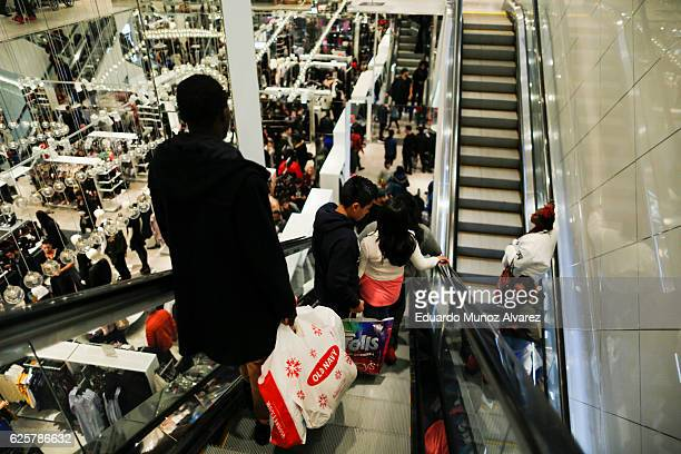 People ride an escalator inside a HM retail store during Black Friday events on November 25 2016 in New York City The day after Thanksgiving called...