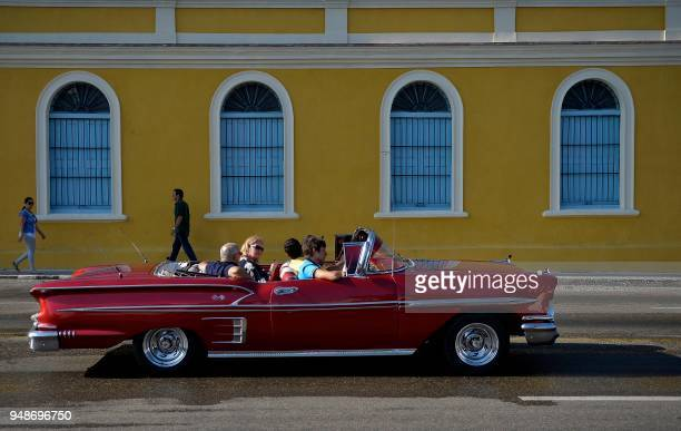 People ride an old American car through the streets of Havana on April 19 day in which Miguel DiazCanel was formally named Cuba's new president and...
