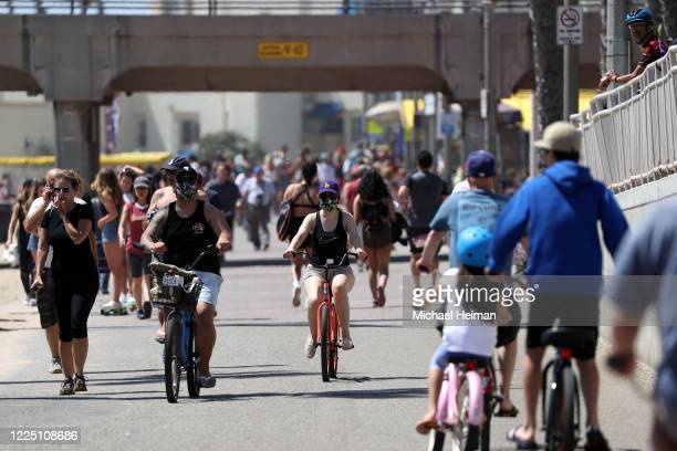People ride and walk on a path along beach amid the coronavirus pandemic on May 15, 2020 in Huntington Beach, California. Beaches across the state...