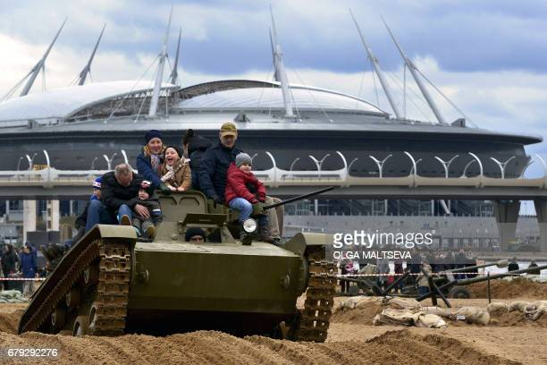 People ride atop a military vehicle during a military historical festival with the new 'Saint Petersburg' football stadium also known as Krestovsky...