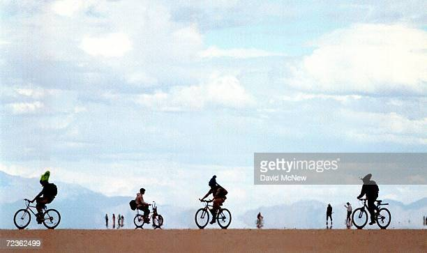 People ride bicycles against a backdrop of mirages September 2 2000 at the15th annual Burning Man festival in the Black Rock Desert near Gerlach...