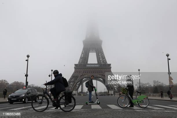 TOPSHOT People ride bicycles and electric scooter past the Eiffel tower partially hidden by fog on December 5 2019 in Paris as the monument is closed...