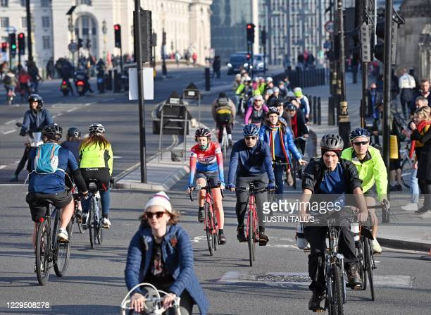 People ride bicycles in the cycle lane as they cross Westminster Bridge into Parliament Square in London on November 7, 2020. - The roads in central...