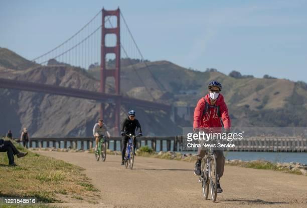 People ride bicycles near the Golden Gate Bridge amid the coronavirus outbreak on April 27, 2020 in San Francisco, California. The Coronavirus...