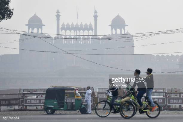 People ride bicycles past a man standing next to an autorickshaw on a road shrouded in smog in New Delhi India on Saturday Nov 11 2017 Thick toxic...