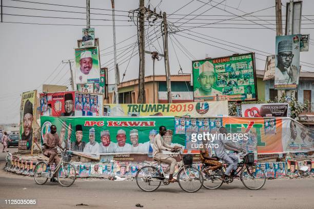 People ride bicycles past electoral posters and billboards in the Nigerian city of Mubi Adamawa State on February 15 on the eve of the country's...