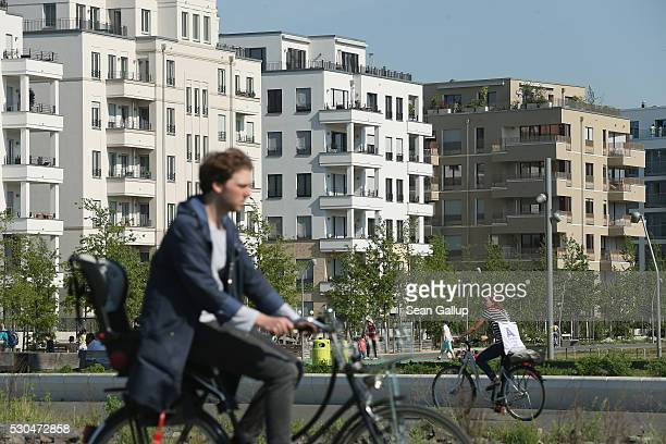 People ride bicycles past newlycompleted apartment buildings at Gleisdreieck park in the city center on May 11 2016 in Berlin Berlin Berlin is...