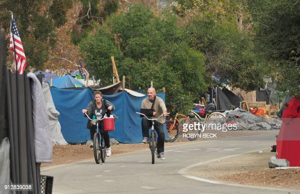 People ride bicycles past tents and tarps of a homeless encampment along the Santa Ana River bicycle path near Angel Stadium in Anaheim California...