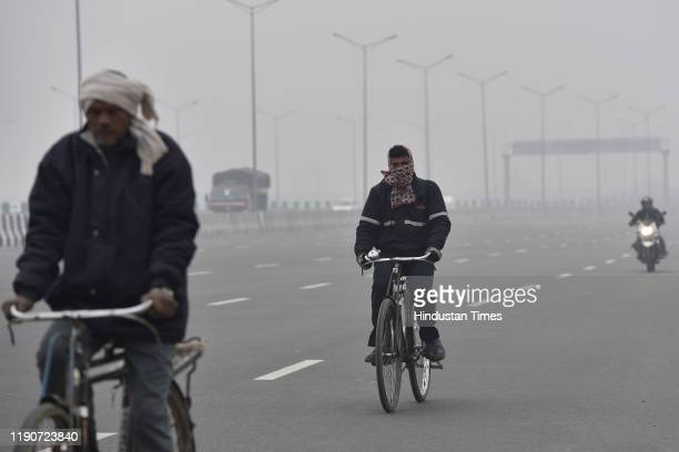 People ride bicycles wearing warm clothes on a cold morning, at Sarai Kale Khan, on December 29, 2019 in New Delhi, India. Severe cold wave...