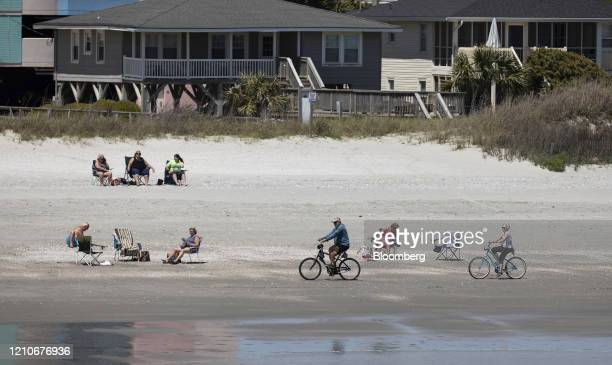 People ride bikes along the shore in Cherry Grove Beach South Carolina US on Wednesday April 22 2020 Governor Henry McMaster said he was forming an...