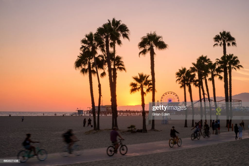 People ride bikes and walk along the beach at sunset in Santa Monica, California. : Foto de stock
