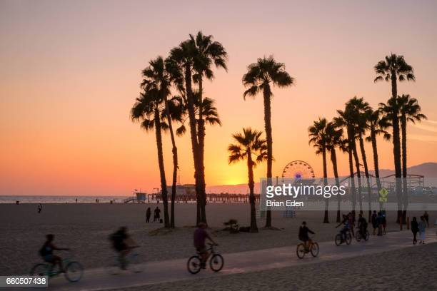 people ride bikes and walk along the beach at sunset in santa monica, california. - los angeles foto e immagini stock