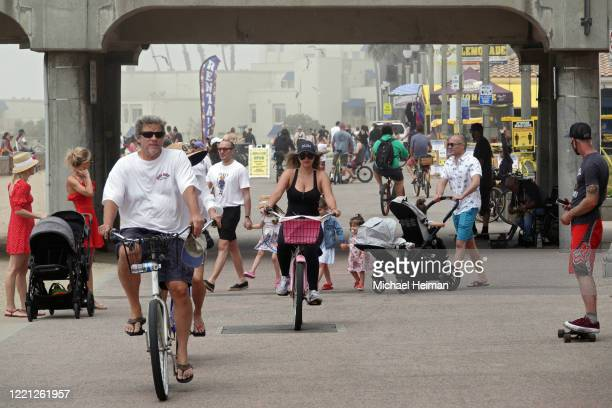 People ride bikes and walk on a path along the beach on April 26 2020 in Huntington Beach California Southern California is expecting summerlike...