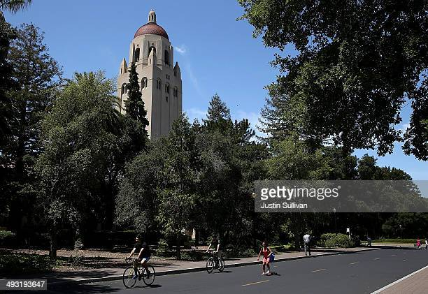 People ride bikes past Hoover Tower on the Stanford University campus on May 22 2014 in Stanford California According to the Academic Ranking of...