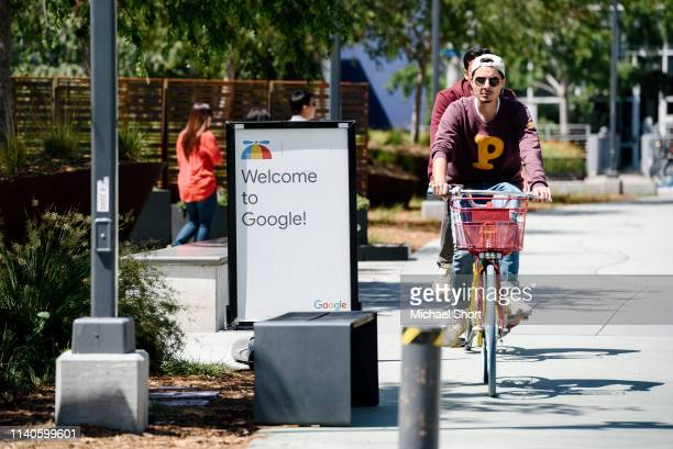 People ride bikes past signage on the Google campus as Google workers inside hold a sitin to protest sexual harassment at the company on May 1 2019...
