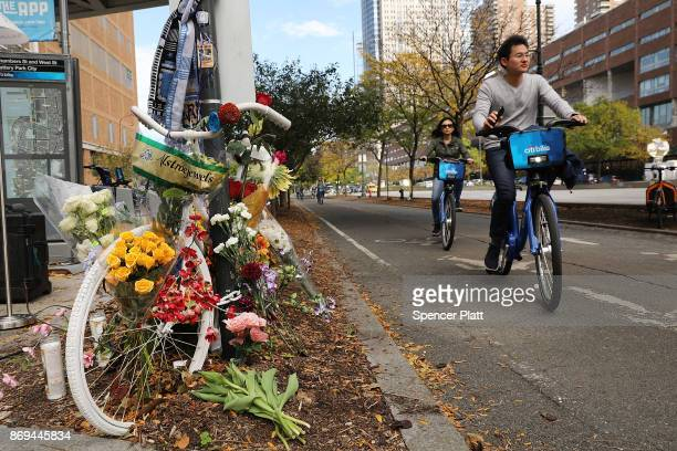 People ride bikes past the scene of Tuesday's terrorist attack along a bike path in lower Manhattan on November 2 2017 in New York City Eight people...