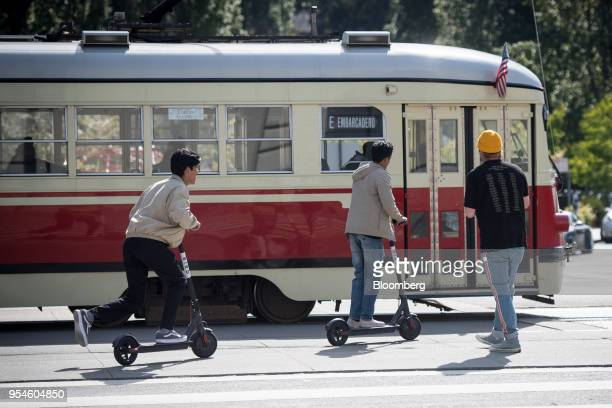 People ride Bird Rides Inc shared electric scooters past a trolley on the Embarcadero in San Francisco California US on Thursday May 3 2018 City...