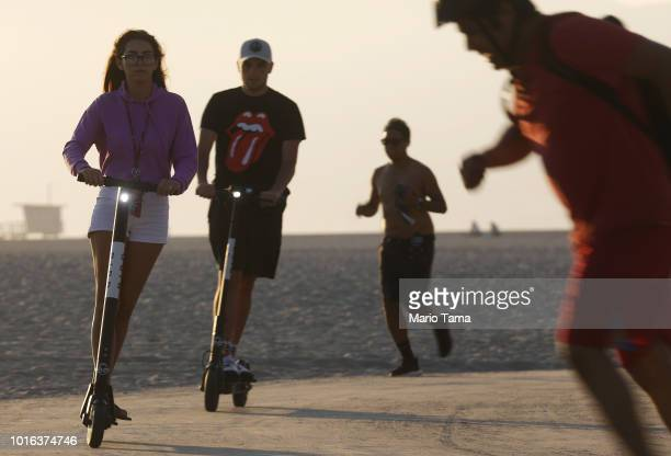 People ride Bird shared dockless electric scooters along Venice Beach on August 13 2018 in Los Angeles California Shared escooter startups Bird and...