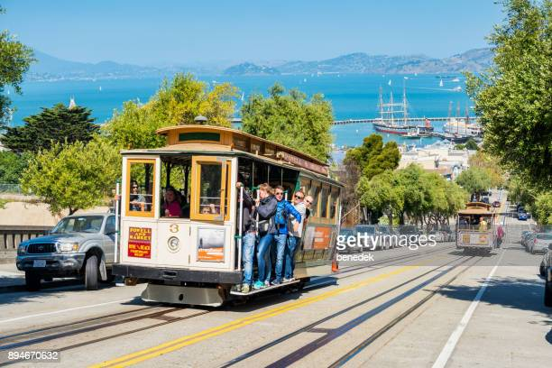 people ride cable car in san francisco - cable car stock pictures, royalty-free photos & images