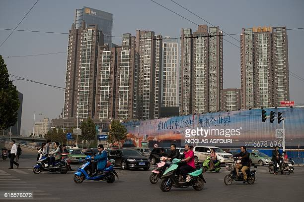 People ride electric bikes as they pass next to property condeminiums in Zhengzhou on October 19 2016 China's growth slipped to a sevenyear low of 66...