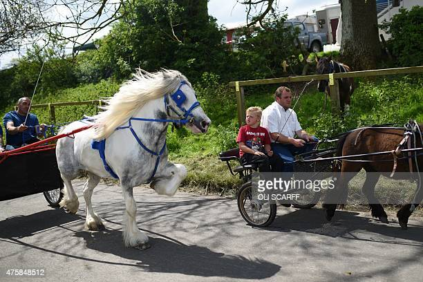 People ride horsedrawn carriages along a road on the opening day of the annual Appleby Horse Fair in the town of ApplebyinWestmorland North West...