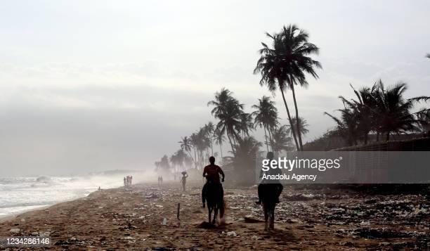 People ride horses on a beach in Abidjan, Ivory Coast on July 28, 2021.