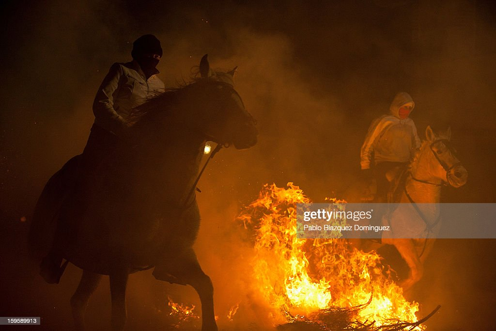 People ride horses through a bonfire on January 16, 2013 in San Bartolome de Pinares, Spain. In honor of San Anton, the patron saint of animals, horses are riden through the bonfires on the night before the official day of honoring animals in Spain.