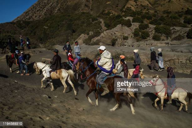 People ride horses to the top of Mount Bromo, East Java. Bromo is the most famous mountain in East Java with the busiest visits every year. Mount...