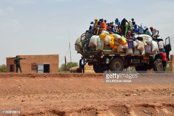 TOPSHOT People ride in a loaded truck on June 19 by the police checkpoint where two policemen were killed and four injured by armed men during an...