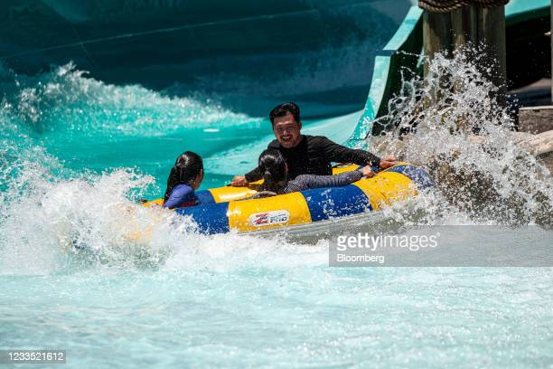 People ride in a tube at Six Flags Hurricane Harbor water park in Concord, California, U.S., on Thursday, June 17, 2021. Californiaavoided blackouts...