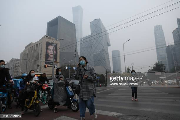 People ride in smog at the CBD area on October 20, 2020 in Beijing, China.
