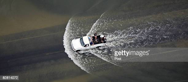 People ride in the back of a pickup truck through floodwaters from Hurricane Ike September 14, 2008 in High Island, Texas. Floodwaters from Hurricane...
