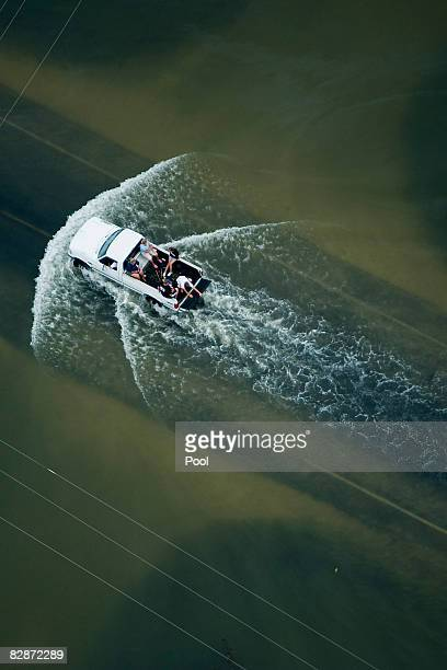 People ride in the back of a pickup truck through floodwaters from Hurricane Ike September 14, 2008 in High Island, Texas. Hurricane Ike made...