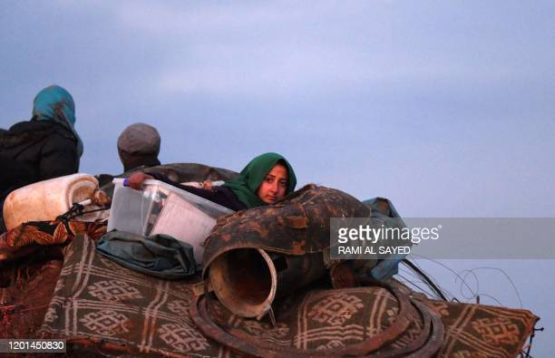 People ride in the back of a truck with furniture, mattresses, and blankets while passing by an internally-displaced persons camp by Dayr Ballut near...