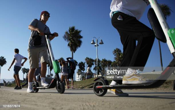 People ride Lime shared dockless electric scooters along Venice Beach on August 13 2018 in Los Angeles California Shared escooter startups Bird and...