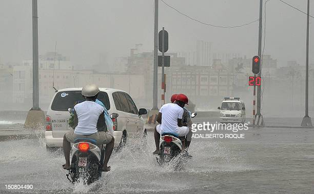 People ride motorbikes in a flooded street in Havana on August 26 following the passage of tropical storm Isaac With winds reaching 50 miles per hour...
